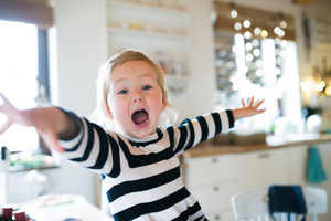 Cute little blond girl in striped dress sitting on kitchen table, shouting, arms stretched. Christmas season.