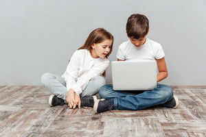 Cute little boy and girl sitting and using laptop together