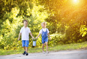 Cute little boy and girl taking a walk outside in nature on a sunny summer day