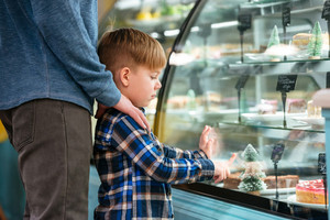 Cute little boy and his father standing and choosing cake in showcase at supermarket