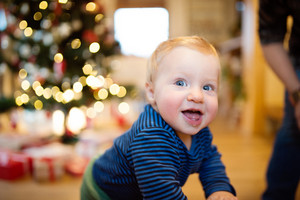 Cute little boy at home against Christmas tree and presents