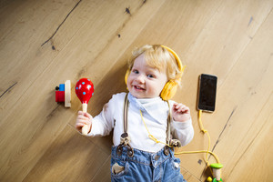 Cute little boy at home lying on wooden floor wearing headphones, listening music from smart phone and playing musical instrument.