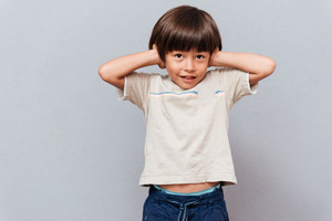 Cute little boy covered ears by hands over gray background