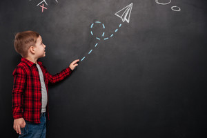 Cute little boy dressed in shirt in a cage looking at arrow drawn on chalkboard and pointing on it.