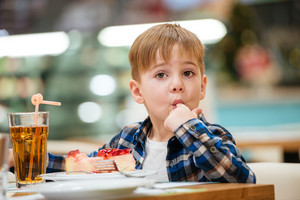 Cute little boy eating cake and drinking juice in cafe