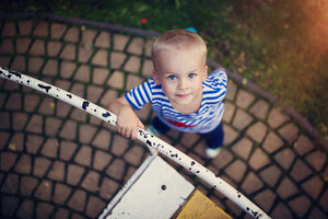 Cute little boy in a park on an old carousel.