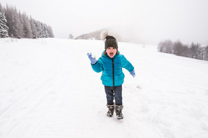 Cute little boy in blue jacket and hat playing outside in snow in winter nature, throwing snow ball, shouting