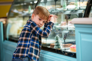 Cute little boy leaning at showcase and choosing cake at supermarket
