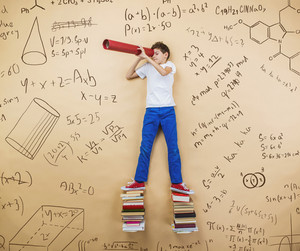 Cute little boy learning playfully in frot of a big blackboard. Studio shot on beige background.
