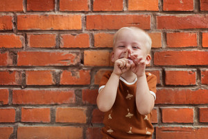 Cute little boy making funny faces on a brick wall background
