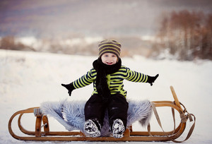Cute little boy on sledge having fun outside in the snow in winter.