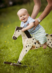 Cute little boy on the rocking horse outside