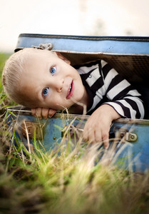 Cute little boy playing in the old suitcase