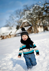 Cute little boy playing outside in the snow in winter.