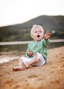 Cute little boy playing with the sand by the lake