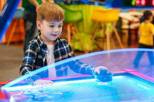 Cute little boy standing and playing air hockey at indoor amusement park