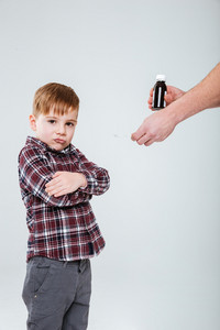 Cute little boy standing with arms crossed and refusing to take a medicine