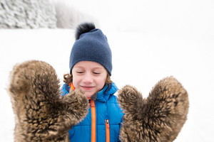 Cute little boy wearing big furry gloves outside in winter nature