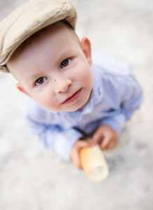 Cute little boy wearing flat cap, holding bun standing against asphalt path.