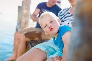 Cute little boy with his parents sitting on the pier on sunny summer day