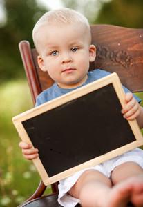 Cute little boy with little blackboard sitting on chair in meadow