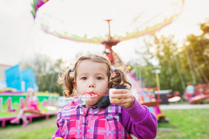 Cute little daughter blowing bubbles, family in amusement park, fun fair