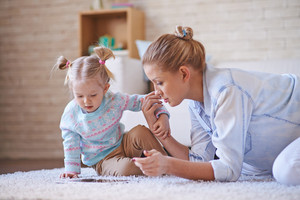 Cute little girl and young woman using digital tablet while spending time at home