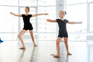Cute little girl ballerina dancing with her teacher in dance studio