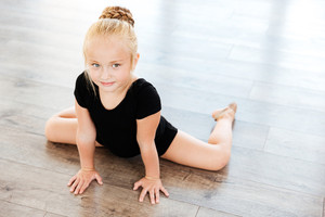 Cute little girl ballerina stretching on the floor in dance studio