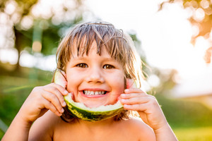 Cute little girl eating watermelon outside in garden, sunny summer back yard