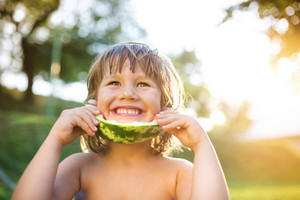 Cute little girl eating watermelon outside in summer garden