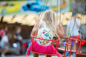 Cute little girl enjoing time at fun fair, chain swing ride, amusement park in summer. Rear view.