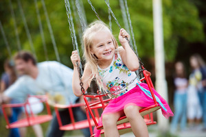 Cute little girl enjoing time at fun fair, chain swing ride, amusement park in summer