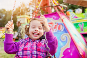 Cute little girl enjoing time at fun fair, chain swing ride, amusement park