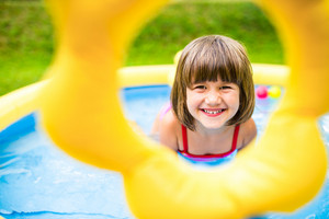 Cute little girl having fun in garden swimming pool. Sunny summer day at the backyard