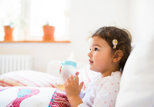 Cute little girl holding bottle with tea at home sitting on sofa in living room