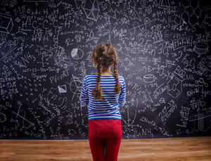 Cute little girl in front of big blackboard