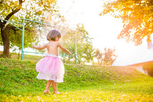 Cute little girl in pink princess skirt running in green sunny summer garden