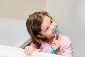 Cute little girl in pink pyjamas in bathroom brushing her teeth