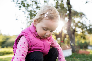 Cute little girl in pink sweatshirt and vest outside in nature on a sunny day, squatting down