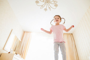 Cute little girl in pink t-shirt with two braids in bedroom jumping on a bed