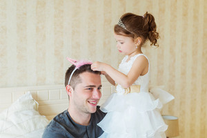 Cute little girl in princess dress putting pink crown on her father head