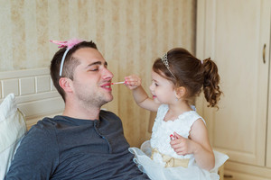 Cute little girl in princess dress that is putting on colorful make up on her father