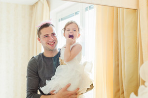 Cute little girl in princess dress that putt on colorful make up on her father, looking into a mirror
