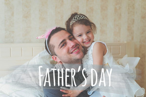Cute little girl in princess dress with her father wearing crowns, smiling. Fathers day concept.