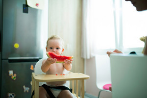 Cute little girl in the kitchen sitting in high chair eating watermelon
