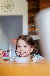 Cute little girl in the kitchen smiling, eating spaghetti
