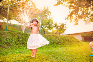 Cute little girl in white princess skirt dancing and running in green sunny summer garden