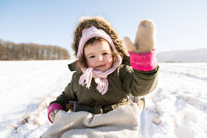 Cute little girl outside in winter nature on sunny day, sitting on sledge, waving