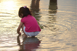 Cute little girl play in the water at the beach